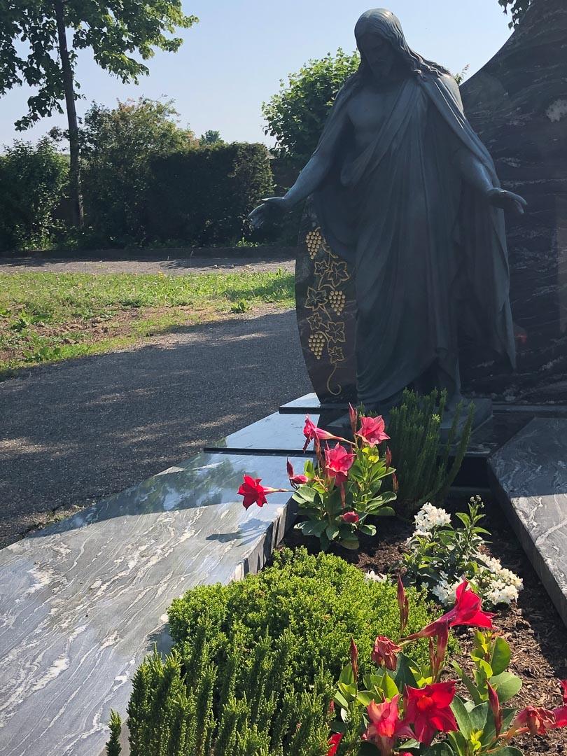 Blick auf Statue auf dem Abenheimer Friedhof mit roten blühenden Blumen