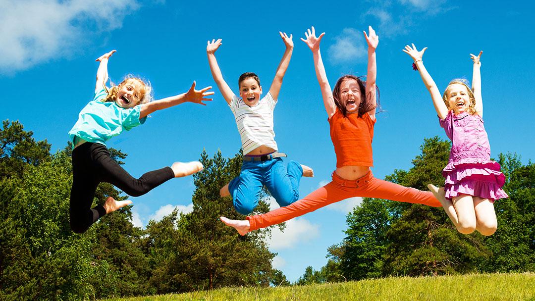 Hochspringende Kinder im Sommer auf Wiese mit Bäumen ©Shmel - stock.adobe.com